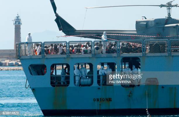 Migrants sit on the deck of the Italian navy ship Orione as the ship enters the port of Valencia on June 17 2018 The Aquarius rescue ship with more...