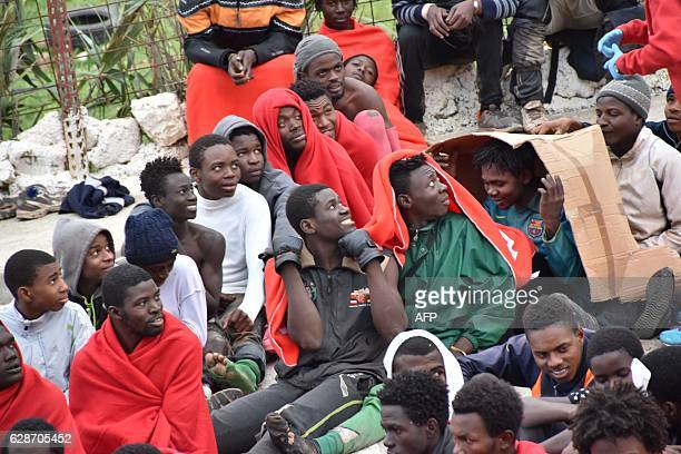 Migrants sit on the ground in El Tarajal Ceuta close to the boarder with Morocco on December 9 2016 after being rounded up by police to be attended...