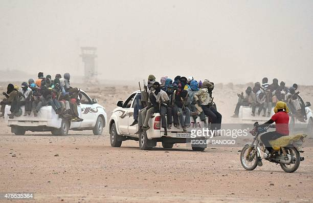 Migrants sit on the open cargo of pickup trucks holding wooden sticks tied to the vehicle to avoid falling from it as they leave the outskirts of...