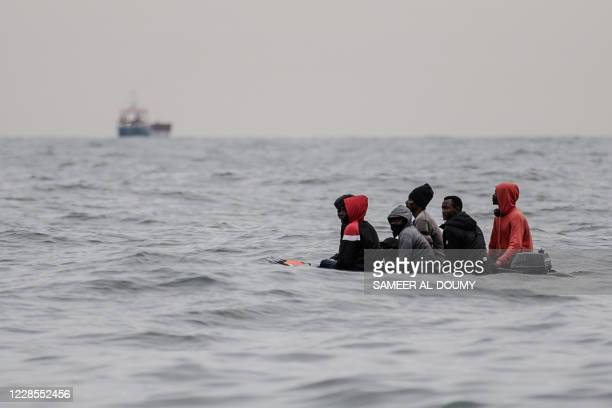 Migrants sit onboard a boat navigating in agitated waters between Sangatte and Cap Blanc-Nez , in the English Channel off the coast of northern...