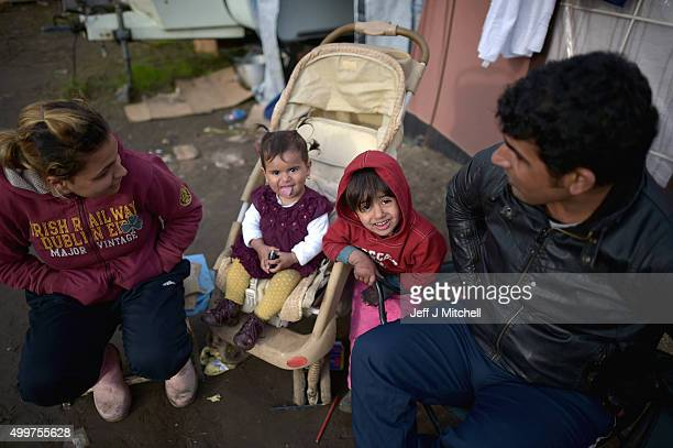 Migrants sit outside there living space in the camp known as the 'New Jungle' on December 3 2015 in Calais France Thousands of migrants continue to...