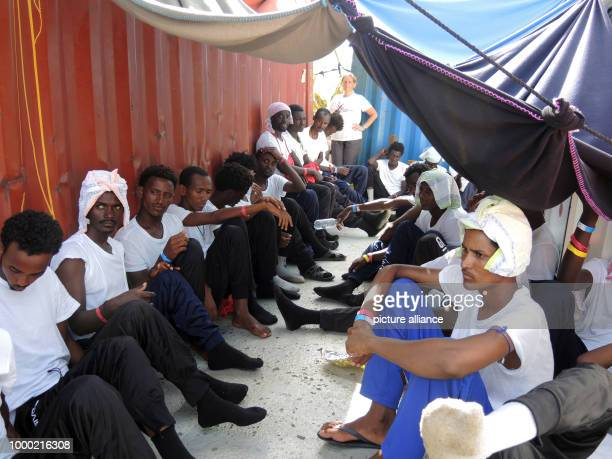 Migrants sit protected from the sun by tarpaulins on board the rescue ship 'Aquarius' which is bringing them to Italy 28 June 2017 The aid...