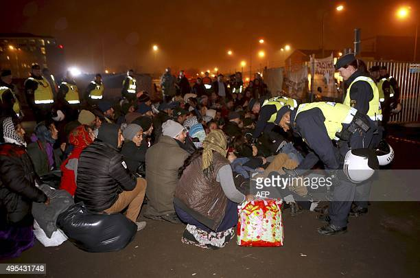 Migrants sit surrounded by police offivers before leaving an illegal camp set up in Malmoe on November 3 after the police started clearing the Roma...