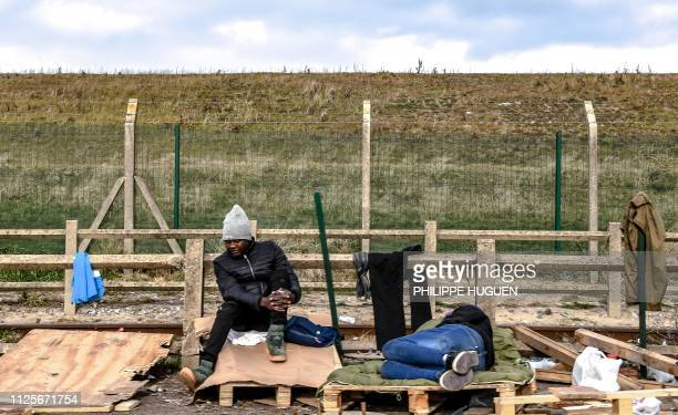 Migrants sit under the winter sun close to their make shift camp in the vicinity of the former 'Jungle' camp site, near the northern French port city...