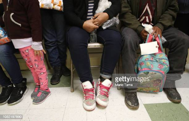 Migrants sit with their belongings as they are received at an Annunciation House shelter for migrants on October 12 2018 in El Paso Texas Annuciation...