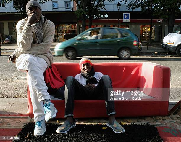 Migrants sits on a red sofa near the Stalingrad metro station in a makeshift camp prior to the site being dismantled by authorities on November 2...