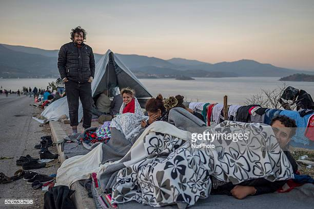 Migrants sleep on a road on the Greek Island of Lesbos after crossing the Aegean sea from Turkey on October 16, 2015 More than 400,000 refugees,...