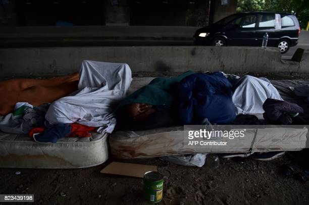 Migrants sleep on mattresses laying on the ground beside highways at a makeshift camp near a humanitarian centre for migrants in the La Chapelle area...