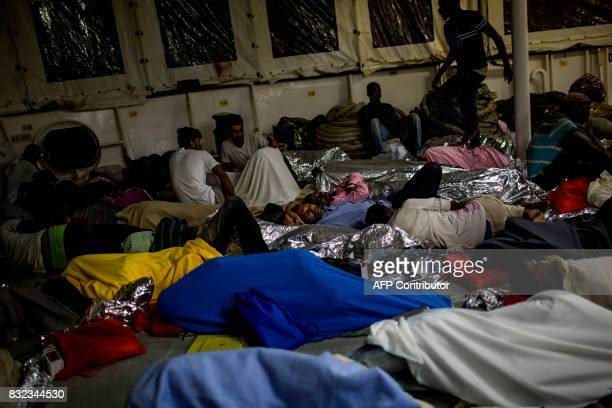 TOPSHOT Migrants sleep on the deck of the Aquarius rescue ship run by NGO SOS Mediterranee and Medecins Sans Frontieres after their transfer from the...