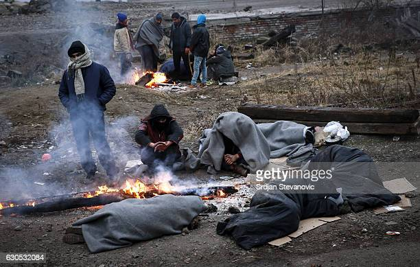 A migrants sleep wrapped in the blankets near a makeshift shelter in an abandoned warehouse on December 23 2016 in Belgrade Serbia Hundreds of...