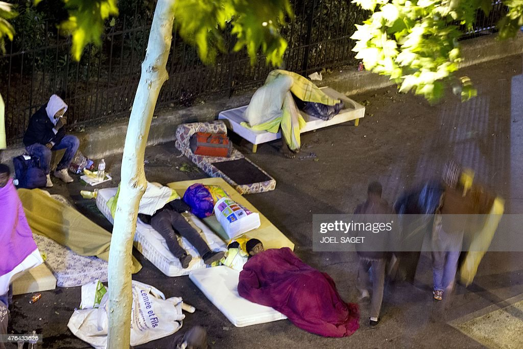 Migrants, some with mattresses, try to find a place to sleep on Place de la Chapelle in a northern Paris district late on June 8, 2015. Migrants, most of them from Sudan, who were living in makeshift camps near this area, have been evacuated on June 2 and June 8. The European Commission is ready to discuss new ways to admit and distribute asylum seekers in the EU, its top migration official said last week, after Paris and Berlin urged it to rethink its plans.