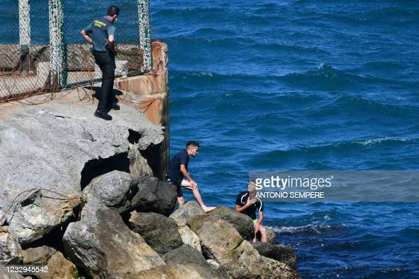 Migrants speak with a Spanish Civil guard after swimming to the Spanish enclave of Ceuta from neighbouring Morocco on May 17, 2021. - More than 80...