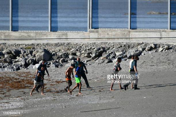 Migrants speak with Spanish Civil guards after swimming to the Spanish enclave of Ceuta from neighbouring Morocco on May 17, 2021. - More than 80...