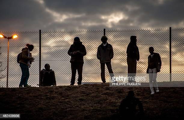 Migrants stand against a chain link fence inside the Eurotunnel site in Coquelles near Calais northern France on July 30 2015 French authorities said...