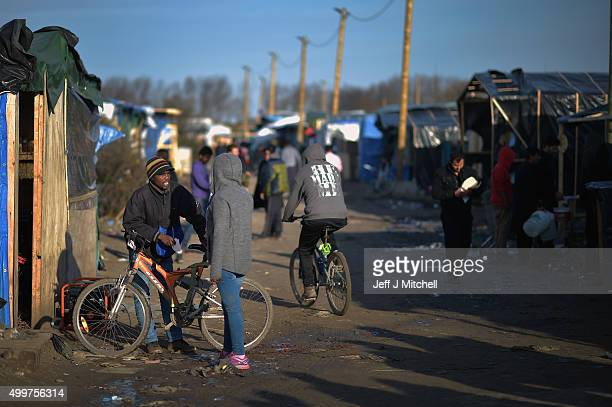 Migrants stand and talk to one another in the camp known as the 'New Jungle' on December 3 2015 in Calais France Thousands of migrants continue to...