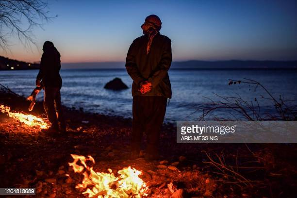 TOPSHOT Migrants stand around a fire to get warm as they have been blocked for two days on a beach in northern Lesbos on March 2 2020 Some 1300...