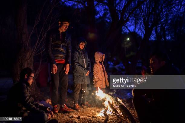 Migrants stand around a fire to get warm as they have been blocked for two days on a beach in northern Lesbos on March 2 2020 Some 1300 arrived at...