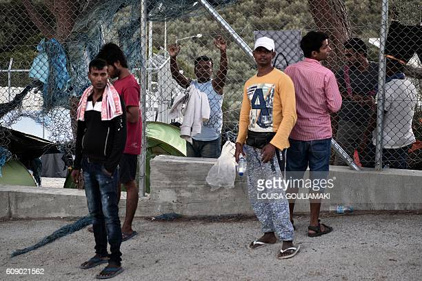 Migrants stand at the Moria camp on the island of Lesvos on September 20, 2016. Thousands of migrants were forced to flee to safety on September 19...