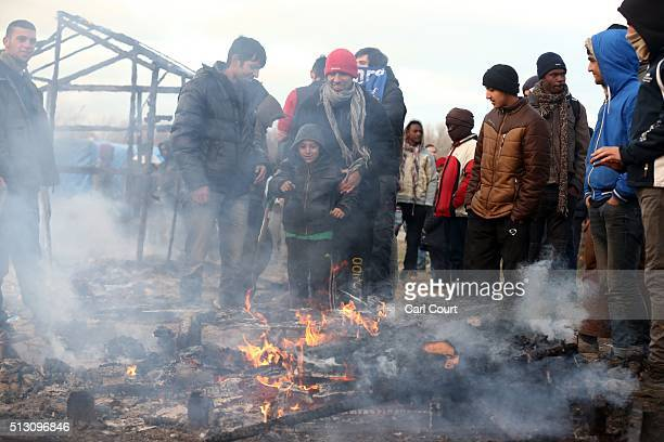 Migrants stand behind a smouldering tent as part of the 'jungle' migrant camp is cleared on February 29 2016 in Calais France The French authorities...