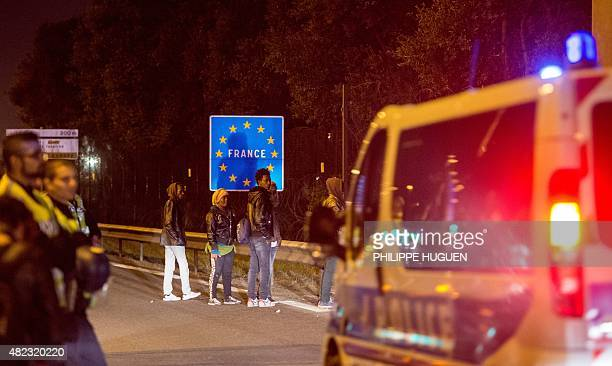 Migrants stand in front of a road sign for France on the Eurotunnel site in Coquelles near Calais northern France on early July 30 2015 One man died...
