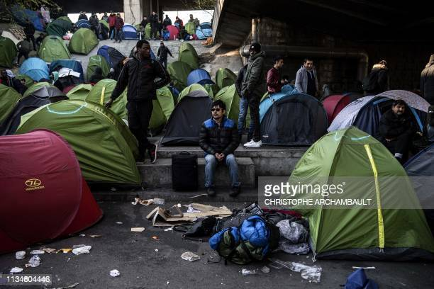 Migrants stand in front of tents as police officers and security agents carry out an evacuation of a makeshift camp at Porte de la Chapelle in the...