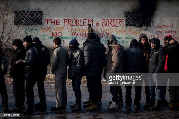 TOPSHOT Migrants stand in line for food outside of a derelict warehouse used as a makeshift shelter near Belgrade's main railway station on January...