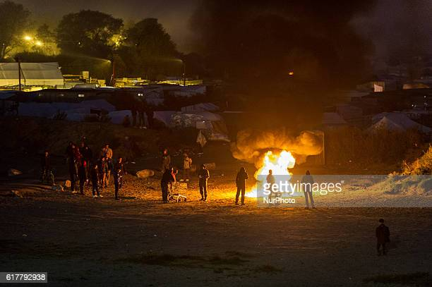 Migrants stand in the Calais Jungle at a fire in Calais France on 2016 The refugee camp on the coast to the English Channel is to be cleared today...