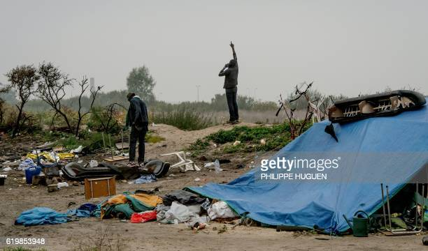 TOPSHOT Migrants stand in the 'Jungle' migrant camp in Calais northern France on November 1a day after a massive operation to clear the squalid...