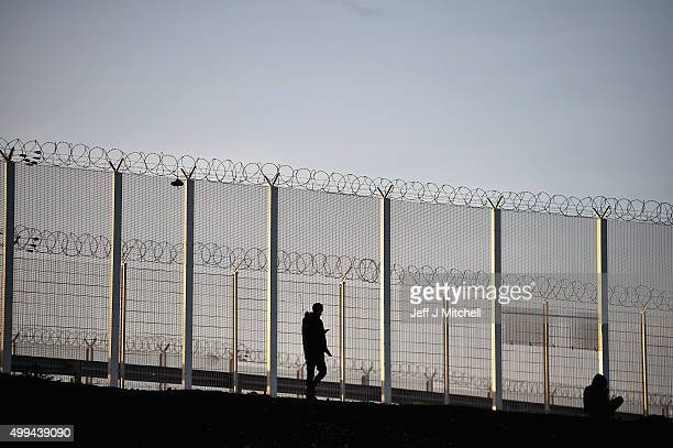 Migrants stand next to a fence erected near the camp known as the 'New Jungle' on December 1 2015 in Calais France Thousands of migrants continue to...