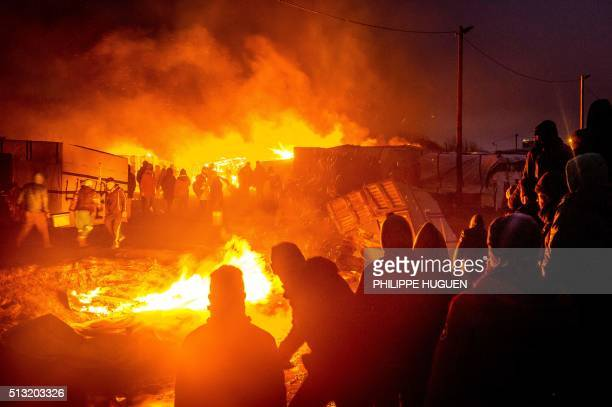 TOPSHOT Migrants stand next to a fire burning shacks in the southern part of the socalled 'Jungle' migrant camp as half of the camp is being...