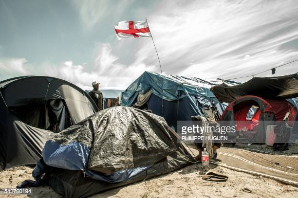 Migrants stand next to a flag of England inside the 'Jungle' camp for migrants and refugees in Calais on June 24 after Britain voted to leave the...