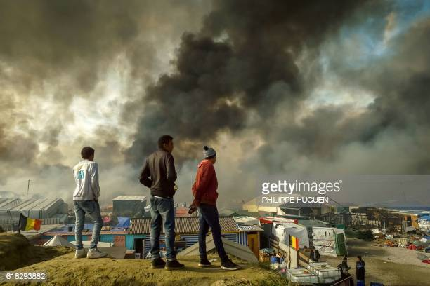 TOPSHOT Migrants stand on a hill overlooking the 'Jungle' migrant camp in Calais northern France as smoke rises on October 26 2016 during a massive...