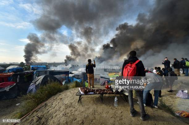 Migrants stand on a hill overlooking the 'Jungle' migrant camp in Calais northern France as smoke rises on October 26 2016 during a massive operation...
