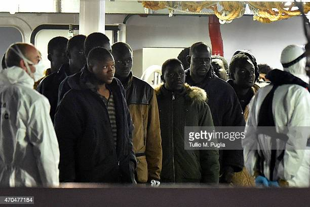 Migrants stand on the deck of the Italian Coast Guard ship Gregretti which is believed to be carrying 27 survivors of the migrant shipwreck in the...