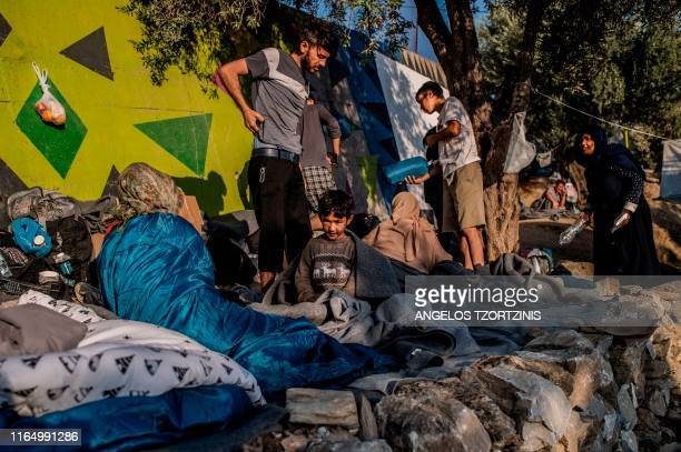 Migrants stand outside at the official refugee camp of Moria on the Greek island of Lesbos, on August 31, 2019. - On August 29 evening, 13 boats...