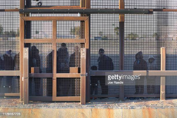 Migrants stand together along the U.S./Mexican border wall as they wait to turn themselves over to the U.S. Border Patrol on February 12, 2019 in El...