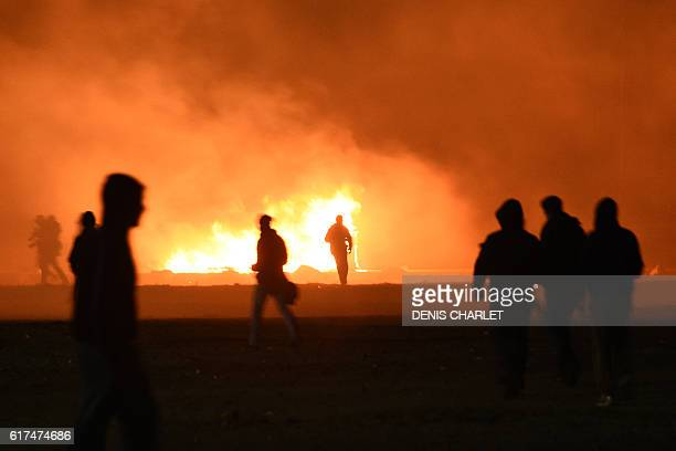 Migrants start a fire during clashes with French police at the 'Jungle' migrant camp in Calais northern France on October 23 2016 on the eve of the...