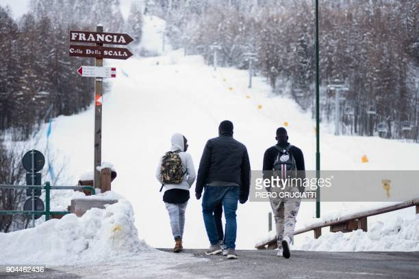 Migrants start to walk in direction of the Colle della Scala a snowcovered pass to cross the border between Italy and France on January 13 2018 near...