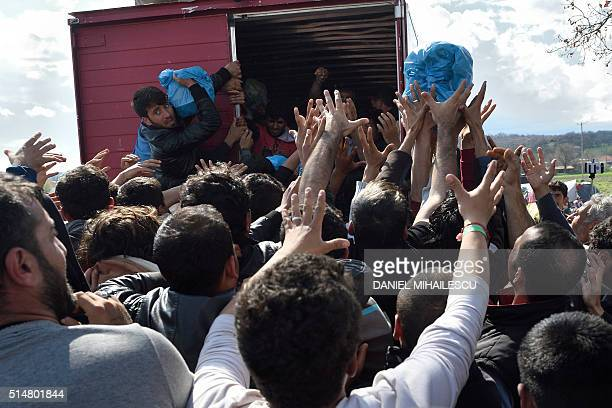 TOPSHOT Migrants strech hands to grab supplies donated by Greek people on March 11 in a makeshift camp at the GreekMacedonian border near the Greek...