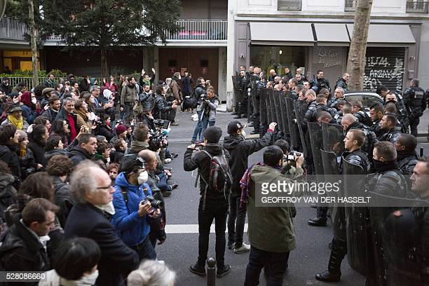 Migrants' supporters face antiriot policemen to protest against the JeanJaur��s highschool evacuation in Paris on May 4 2016 The police evacuated...