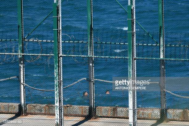 Migrants swim to the Spanish enclave of Ceuta from neighbouring Morocco on May 17, 2021. - More than 80 migrants, including some minors, set off in...