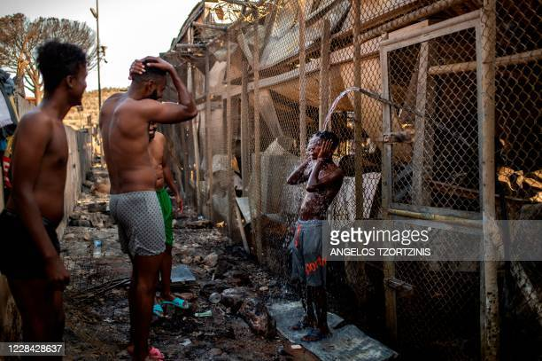 Migrants take shower Children walk in the burnt migrants camp of Moria on the Greek Aegean island of Lesbos on September 9, 2020 after a major fire...