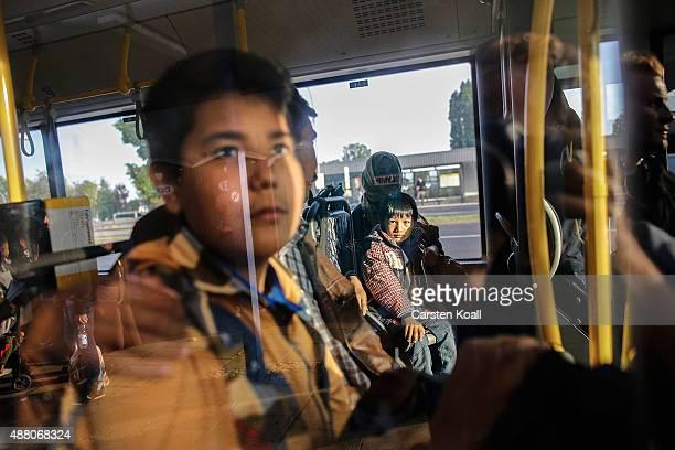 Migrants takes a bus after arriving on an ICE highspeed train of Deutsche Bahn from Munich near Berlin on September 13 2015 in Schoenefeld Germany In...