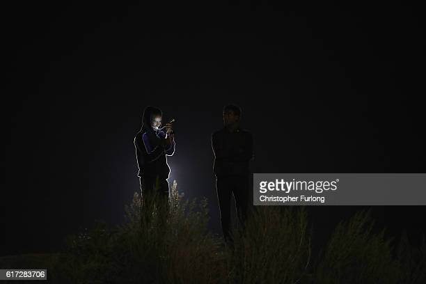 Migrants talk on a mobile phone at the Jungle migrant camp on October 22 2016 in Calais France French authorities are preparing to clear the Jungle...