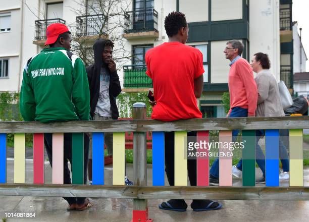 Migrants talk outside the migrants reception center in the Spanish Basque city of Irun on August 9 2018 With migrant arrivals to Spain's southern...