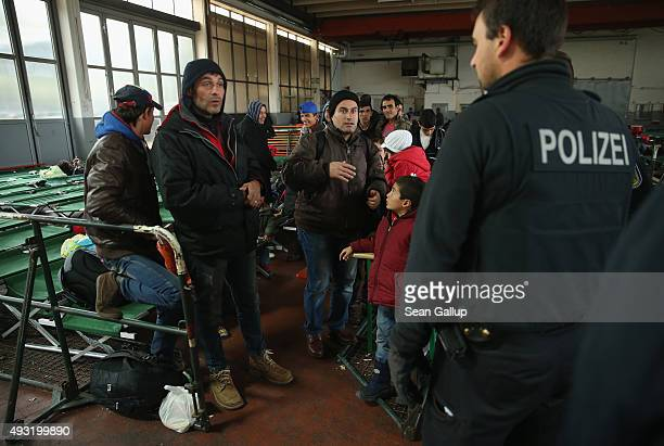 A migrants talks to a German policeman at a temporary shelter on October 17 2015 in Passau Germany According to a German police spokesman...