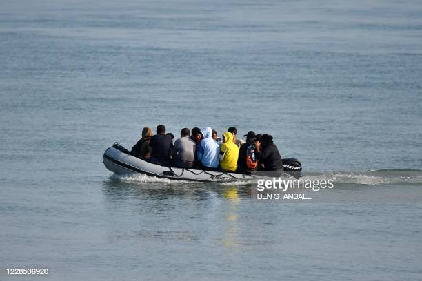 Migrants travel by inflatable boat as they reach the shore near Deal on the south east coast of England on September 14 after crossing the Straits of...
