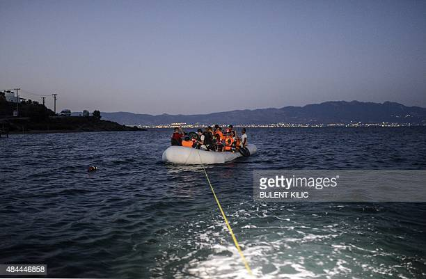 Migrants travel on an inflatable boat to reach the Greek island of Kos as Turkish coast guards try to stop them early on August 19 near the shore of...