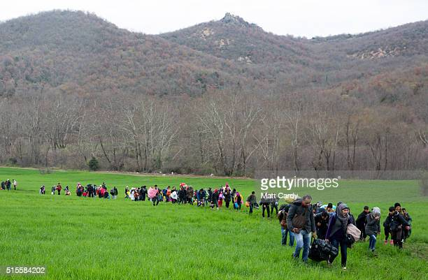 Migrants trek towards Macedonia after leaving the Idomeni refugee camp on March 13 2016 in Idomeni Greece The decision by Macedonia to close its...