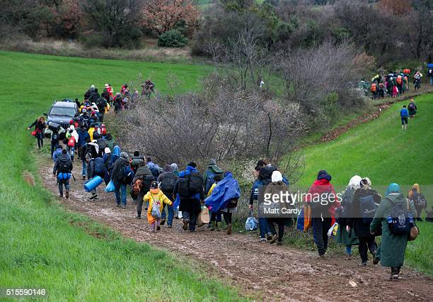 Migrants trek towards Macedonia after leaving the Idomeni refugee camp on March 14 2016 in Idomeni Greece The decision by Macedonia to close its...